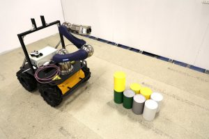 A ground robot inspecting some simulated nuclear material objects