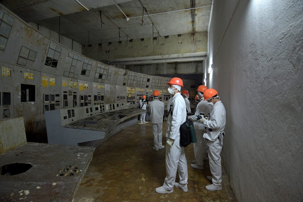 University of Bristol researchers standing inside the control room of Chornobyl Reactor 3.